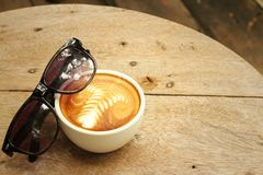 Coffee with sun glasses on background of wooden. Stock Image