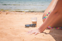 Coffee and sunglasses on the sand. By the sea Stock Photo