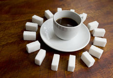 Coffee surrounded. Cup of coffee surrounded by several sugar lumps Royalty Free Stock Image