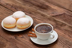 Coffee and sweet donuts. Sweet donut with a cup of coffee for breakfast topped with a hint of the smell of cinnamon. Love the sweet moments together in Stock Photography