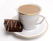 Coffee and sweet pastry. Sweet chocolate square pastry on a white saucer next to coffee cup Royalty Free Stock Image