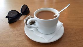 Coffee and sweets. Cup of coffee americano with spoon on the table with sunglasses near and sweet cake or chocolate cake little cupcake good morning America stock image