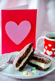 Coffee and sweets for the one I love. A heart gift card and a heart decorated mug of coffee, along with a chocolate cake whoopee pie and candy hearts Royalty Free Stock Photo