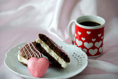Coffee and sweets with a pink heart. A heart decorated mug of coffee, along with a chocolate cake whoopee pie and pink heart Stock Photography