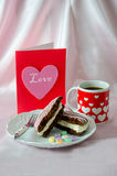 Coffee and sweets with a pink  love heart card. A heart decorated mug of coffee, along with a chocolate cake whoopee pie and pink heart card Royalty Free Stock Photo
