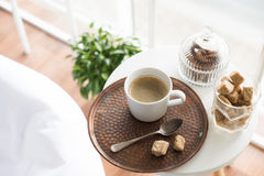 Coffee with sweets served on table in cozy loft room. Interior with large windows, closeup stock photography