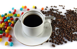 Coffee and sweets. Still life with a cup of coffee, coffee grains and candy allsorts Royalty Free Stock Photography