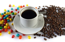 Coffee and sweets. Still life with a cup of coffee, coffee grains and candy allsorts Royalty Free Stock Photos