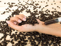 Coffee in syringe and coffee beans on wooden Stock Images