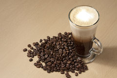 Coffee on the table 2. Coffee with froth and coffee beans below on the table. Horizontal royalty free stock photo