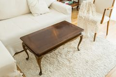 Coffee table in the bright living room with a sofa and vintage decor royalty free stock image