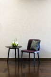 Coffee table Leather chair combination. In front of a plain wall Stock Photo