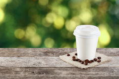 Coffee on table on nature background. Paper cup of coffee on natural outside background with copy space. Coffee on table on nature background. Takeaway coffee Royalty Free Stock Image
