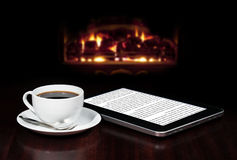 Coffee & tablet. Cap of coffee and tablet on the table top with fireplace in the background royalty free stock photos