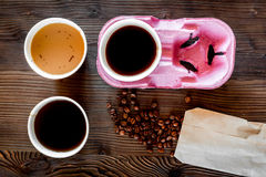 Coffee take away. Coffee cups with covers and coffee beans on wooden table backound top view Stock Photos