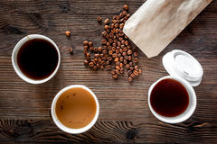 Coffee take away. Coffee cups with covers and coffee beans on wooden table backound top view Stock Image