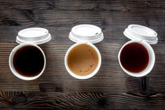 Coffee take away. Coffee cups with covers on wooden table backound top view Stock Photo