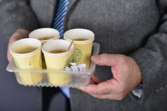 Coffee take away in office. Man, dressed in formal suite holds coffee cups Stock Photography