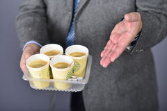 Coffee take away in office. Man, dressed in formal suite holds coffee cups Stock Photos