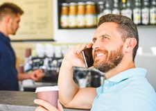 Coffee take away option for busy people. Man mobile conversation cafe barista background. Drink coffee while waiting. Man smartphone order coffee in cafe royalty free stock images