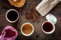 Coffee take out. Coffee cups with covers, coffee beans and cookies on wooden table backound top view Royalty Free Stock Photos