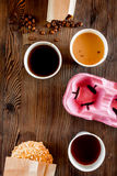 Coffee take out. Coffee cups with covers, coffee beans and cookies on wooden table backound top view copyspace Royalty Free Stock Photos