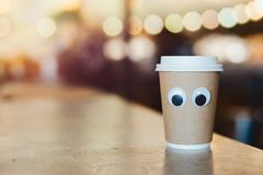 Coffee takeaway cup with cartoon eyes in cafe. Concept of hospitable cafe. And good service. Cute and nice character royalty free stock images
