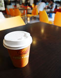 Coffee takeout cup on campus cafe table. A photograph of a paper cup of hot coffee with take out plastic cover attached, placed on dark wood table in a stock photos
