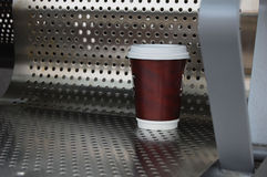 Coffee takeout cup on a silver chair Stock Photos
