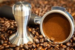 Coffee tamper and portafilter on roasted coffee beans background,coffee powder in the portafilter,prepare of espresso in the. Morning at cafe shop royalty free stock photography