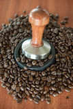 The coffee tamper and roasted coffee in rubber base Stock Images