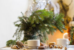 Coffee, tangerines, cookies and nuts in Christmas decor with Christmas tree, nuts and apples on colorful background bokeh Royalty Free Stock Photo