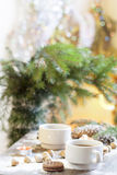 Coffee, tangerines, cookies and nuts in Christmas decor with Christmas tree, nuts and apples on colorful background bokeh Stock Images