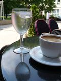 Coffee and tap water. Glass of cold mineral water and cup of coffee on a table in the bar Stock Image
