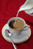 Coffee, tea. Pouring milk in coffee or tea Stock Images