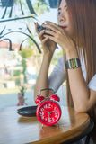 Coffee or Tea Break. Asia girl drink hot coffee or tea break at 02.30 pm in cafe stock photography