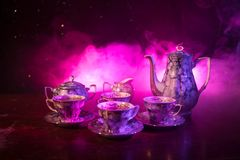 Food background tea and coffee theme. Old vintage ceramic tea or coffee pot with cups jug and sugar cup on dark background with li Stock Photography