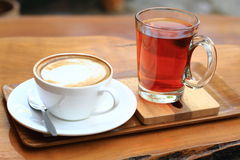 Coffee and tea. Cup of mocha coffee and glass of tea on wood floors Royalty Free Stock Images