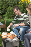 Coffee and tea in the garden. Couple having tea and coffee in the garden on a sunny summerday Stock Photography