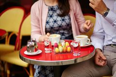 Coffee or tea and macaroons in a Parisian cafe. Couple drinking coffee or tea and eating macaroons in a Parisian cafe Stock Photography