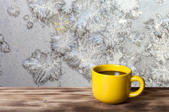 Coffee or tea in yellow cup on the wooden table opposite beautif Royalty Free Stock Images
