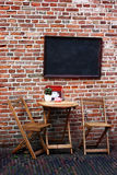 Coffee Terrace. Small wooden table and chairs in front of a brick wall with a black board Stock Images