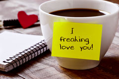 Coffee and text I freaking love you. Closeup of a yellow sticky note with the text I freaking love you attached to a cup of coffee, on a rustic wooden table Royalty Free Stock Images