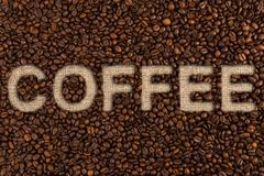 Coffee text on roasted beans and jute bag or sack Stock Images