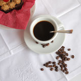 Coffee theme. Close-up of white cup of coffee and coffee beans on white embroidered linen napkin Stock Image