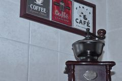 Coffee theme on decorative mural and the old antique manual coffee grinder on background of light tiled wall royalty free stock photo