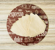 Coffee themed round tray and coffee filters on the wooden backgr Royalty Free Stock Images