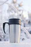 Coffee thermos mug. Heat protection-thermos coffee cup on winter day Stock Images