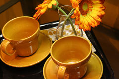 Coffee Time. Two cups on plates with flowers. Orange cups Royalty Free Stock Image