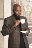 Coffee Time. South African man having a coffee break outside an office building Royalty Free Stock Photo